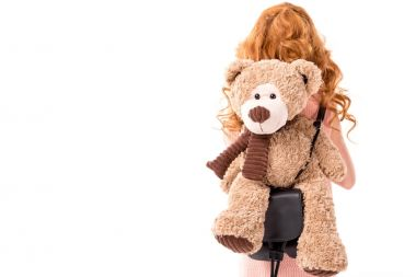 rear view of red hair kid with teddy bear isolated on white