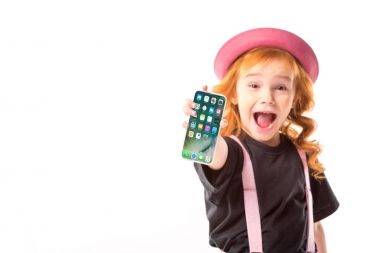 stylish kid in pink hat and suspenders showing smartphone with programs icons isolated on white