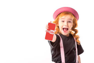 stylish kid in pink hat and suspenders showing smartphone with youtube page isolated on white