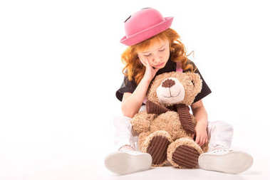 Sad red hair kid sitting with teddy bear on white stock vector