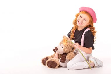 smiling red hair kid sitting with teddy bear and flower on white