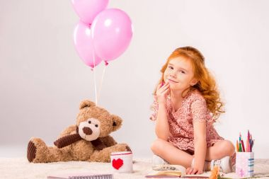 redhead kid sitting on carpet with teddy bear and balloons