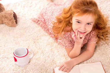 overhead view of dreamy redhead kid lying on fluffy carpet