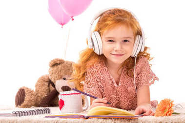 smiling red hair kid in headphones looking at camera isolated on white
