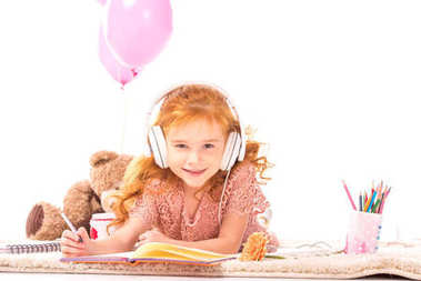 smiling kid drawing and listening music on carpet isolated on white