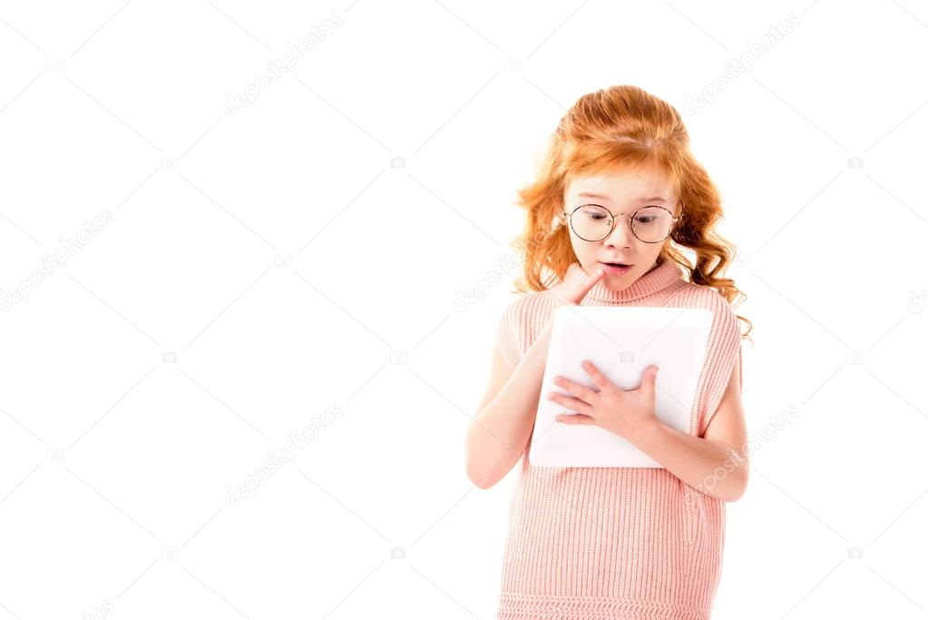 surprised redhead kid looking at tablet isolated on white