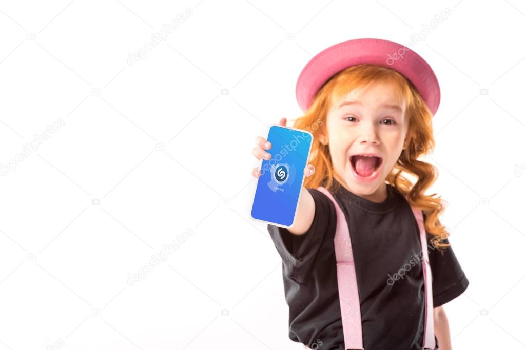 stylish kid in pink hat and suspenders showing smartphone with music program isolated on white