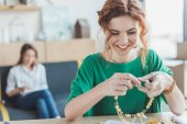 happy young woman making necklace of beads in workshop while her colleague sitting on couch blurred on background