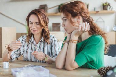 Happy young women working in handmade accessories workshop stock vector