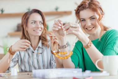 happy young women making necklace at workshop