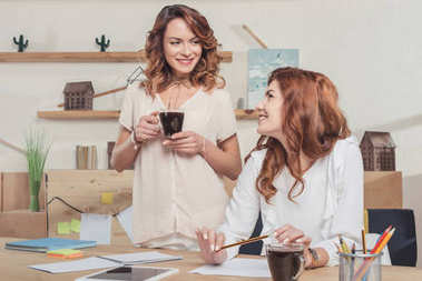 attractive young businesswomen working together at modern office and drinking coffee