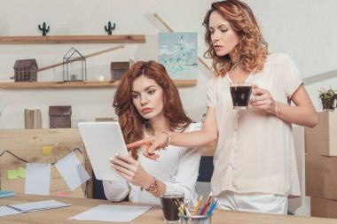 young businesswomen working together while drinking coffee