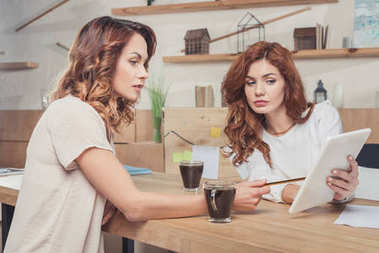 young businesswomen working with tablet together at modern office