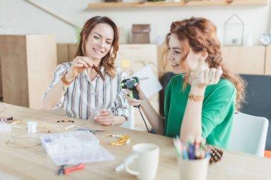 Young women working with glue gun in handmade accessories workshop stock vector