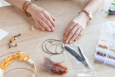 cropped shot of woman with beads and threads for handmade accessories in workshop