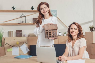 young real estate agents at workplace with wooden house model