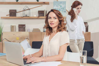 young businesswoman working with laptop at office while her colleague talking by phone