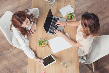 top view of buisnesswomen having lunch together and using devices at office