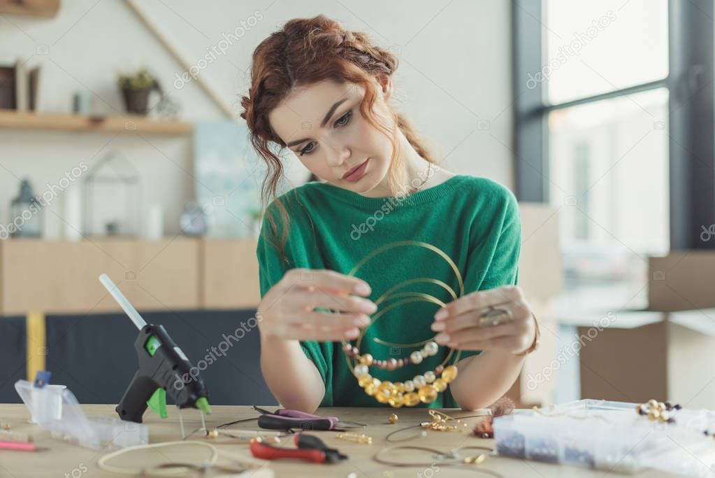 young woman holding handmade necklaces in workshop