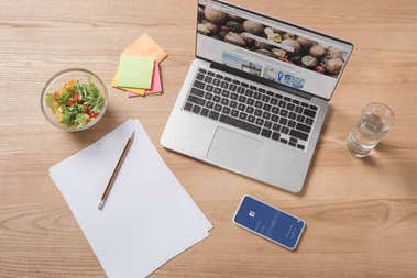 top view of workplace with laptop, smartphone and healthy salad