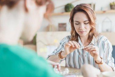 Focused women making accessories at handmade workshop stock vector