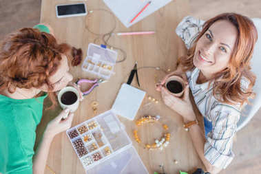 high angle view of happy young women drinking coffee in handmade accessories workshop