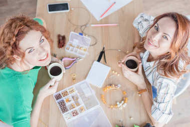 High angle view of young women drinking coffee in handmade accessories workshop stock vector
