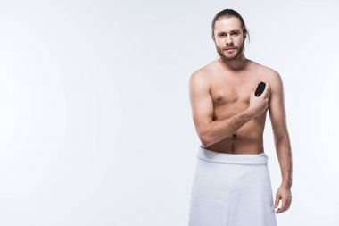cheerful bearded man with bath towel towel on waist holding deodorant spray against his chest, isolated on white