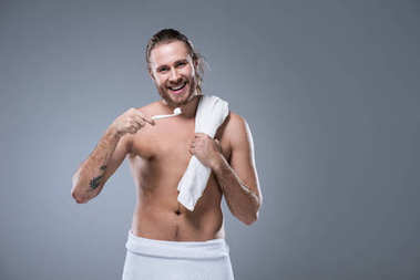 Smiling young man with bath towel on shoulder holding toothbrush with toothpaste in hand, isolated on gray