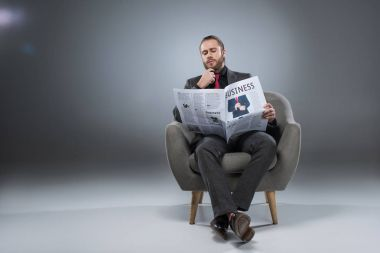 Pensive bearded businessman sitting in armchair and reading newspaper, isolated on gray