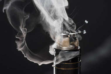 Activating electronic cigarette with clouds of smoke on dark background