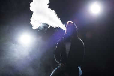 Young bearded man exhaling smoke of electronic cigarette against backlit