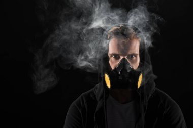 Man in black hood wearing protective filter mask surrounded by clouds of smoke stock vector