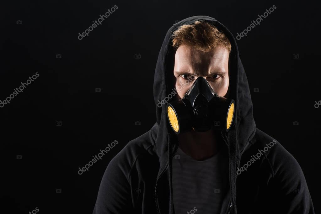 Man in black hood wearing protective filter mask isolated on black