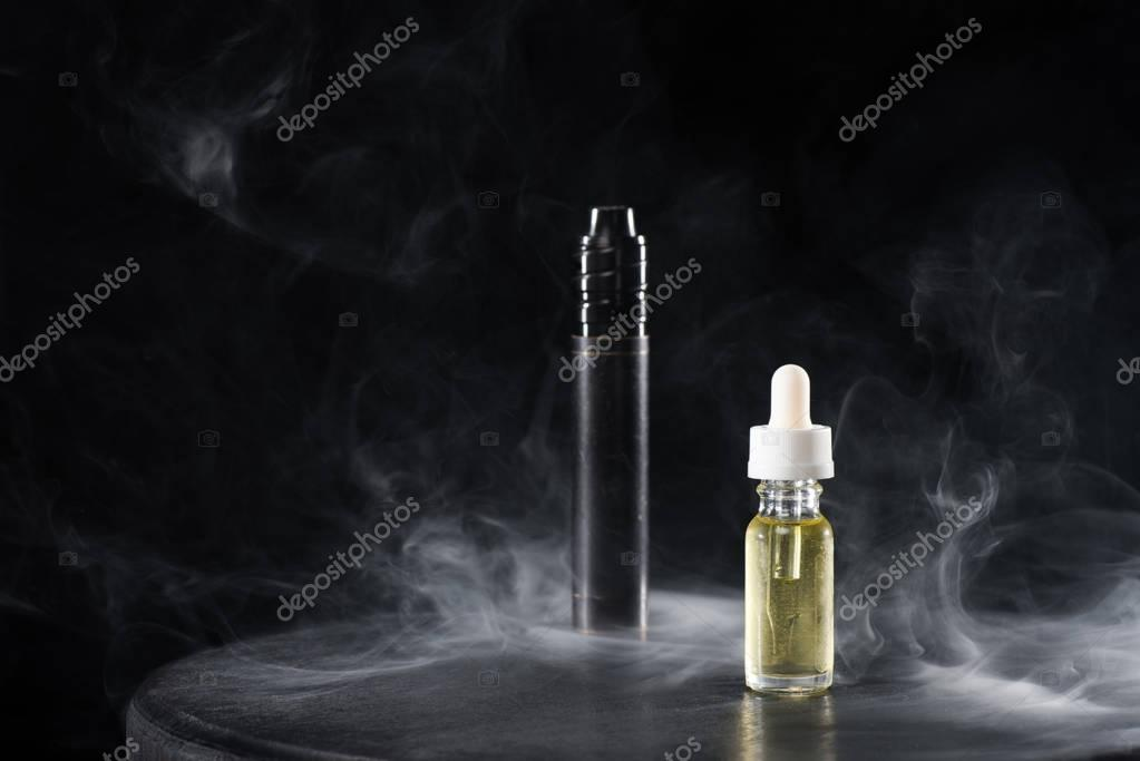 Electronic cigarette and liquid with clouds of smoke on dark background