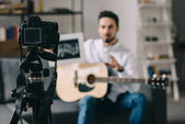 Photo music blogger holding notes and guitar in front of camera