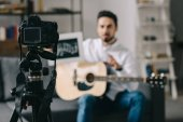Fotografia blogger musica tenendo note e chitarra davanti alla macchina fotografica