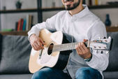 Fotografie cropped image of smiling musician playing acoustic guitar