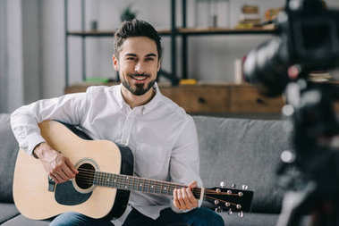 handsome music blogger playing acoustic guitar