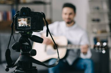 music blogger playing acoustic guitar in front of camera