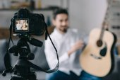 music blogger holding and describing acoustic guitar with camera on foreground
