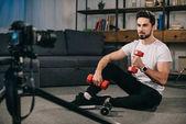 Fotografie Sport-Blogger am Boden und zeigt, wie Sie mit Hanteln trainieren