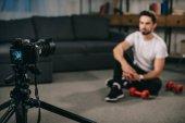 Fotografie sportovní blogger sedí na podlaze a nahrávání nového blogu o činky