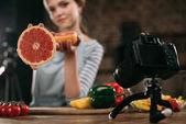 mladí psího zobrazující polovinu grapefruitu na kameru
