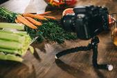 Fényképek digitális fényképezőgép és a fából készült asztal zöldség