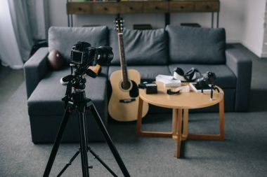 acoustic guitar and cameras with wooden table in empty room