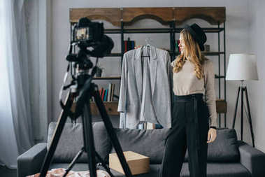 Attractive fashion blogger recording new vlog about jacket stock vector