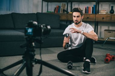 handsome sport blogger recording new blog about dumbbells