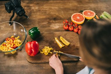 overhead view of female food blogger cutting bell peppers