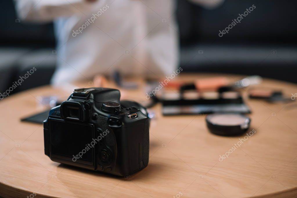 cropped image of beauty blogger near table with cosmetics and camera